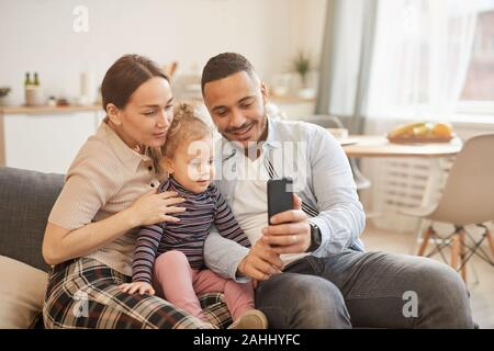 Warm toned portrait of happy mixed-race family taking selfie hoto in home interior, copy space