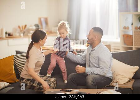 Warm toned portrait of happy modern family playing with cute little daughter in sunlit home interior, copy space