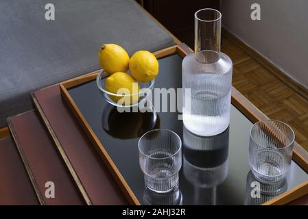Three fresh yellow lemons in a glass bowl, two glasses and carafe with water on modern tray on table, still life - Stock Photo