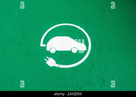 Electric vehicle charging station sign on green road surface background. Top view - Stock Photo