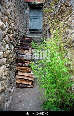 Backstreet with steps to a door and a woodpile ready for winter in the ancient Cathar village of Minerve, Hérault, Occitanie, France - Stock Photo