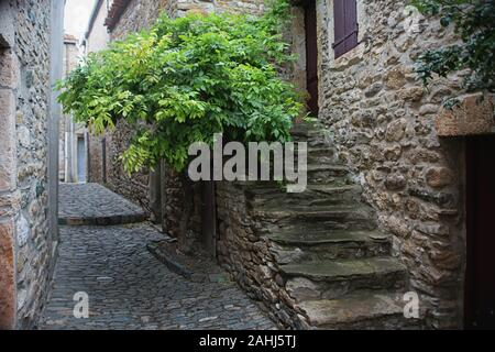 Alley with stone steps (Rue des Martyrs) in the ancient Cathar village of Minerve, Hérault, Occitanie, France - Stock Photo