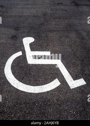 Ein Rollstuhl ist auf einem Parkplatz für Behinderte angebracht. - Stock Photo