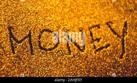 Text money on golden rich sandy background.