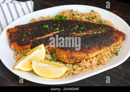 Cajun-style Blackened Red Snapper on Dirty Rice: Blackened red snapper fillet served on a platter of dirty rice with lemon wedges and parsley garnish - Stock Photo