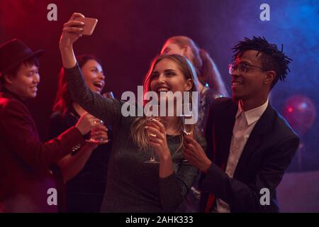 Beautiful mixed-race couple taking selfie photo on dnce floor while enjoying party in night club - Stock Photo