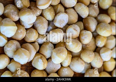 A close-up of delicious raw macadamia nuts on wooden table