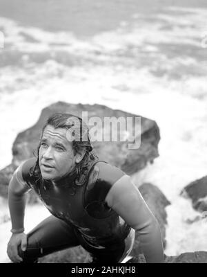 Man in wetsuit climbing up rocks after getting out of water. - Stock Photo