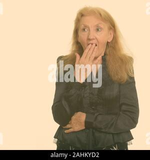 Studio shot of senior businesswoman looking shocked - Stock Photo