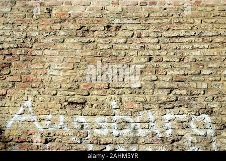 Background from an old historical wall made of burnt bricks, on which the word 'Augsburg' was smeared with white paint