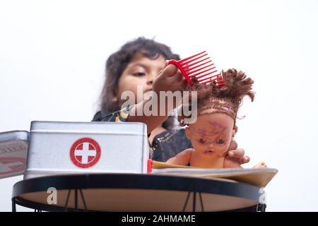 Cute Little Girl Playing hair stylist Beauty Salon with Doll On a white background - Stock Photo