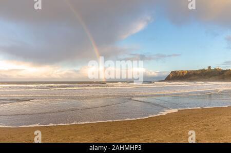 Waves roar towards a beach with a headland in the background and a castle ruin on the skyline.  A rainbow meets the horizon.