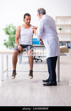 The young male patient visiting experienced doctor - Stock Photo