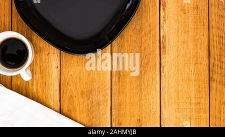 Black plate, white napkin and cup of coffee over wooden table, top view, copy space. Breakfast concept - Stock Photo