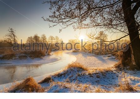 Sun rising behind line of trees on frosty winter morning on the Rawka River, Poland - Stock Photo