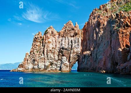 Capo Rosso rocks with an arch culminate the Coastline of Porto Gulf in Corsica Mediterranean Sea, the rocks make  part of Calanques de Piana, Corse-du - Stock Photo