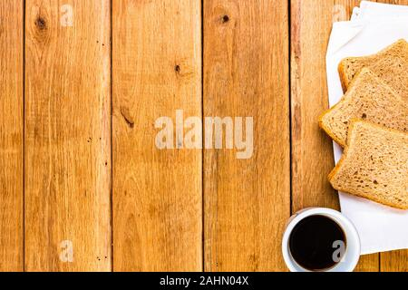 Cup of coffee and wholegrain toast over wooden table, top view, copy space. Breakfast concept - Stock Photo