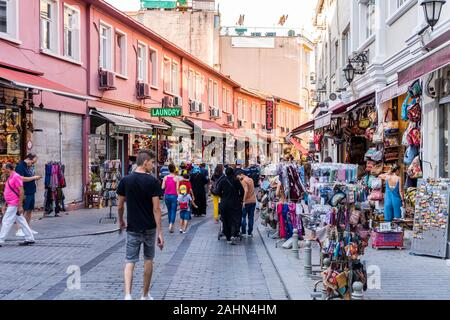 Tourists walk at street in European side with colorful souvenir and gift shops and cafes on a busy summer day of Istanbul, Turkey - Stock Photo