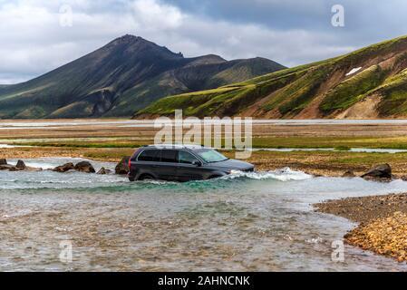 Car crossing Jokulgilskvisl river flow in Fridland ad Fjallabaki Natural park in Highlands of Iceland, approaching Brennisteinsalda camping area in La - Stock Photo