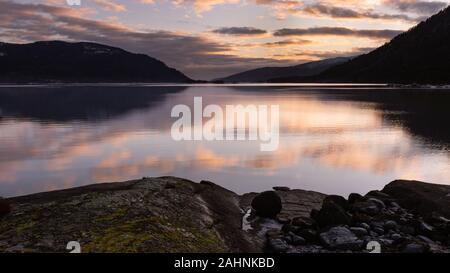 Saturated sunset sky reflected on still, calm fjord lake during a winter, cold day as seen from an island in the centre of the carved valley. - Stock Photo