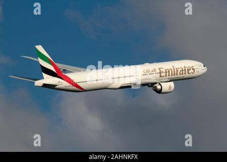 Emirates Boeing 777-300ER long haul passenger jet plane flying in the sky and climbing on departure - Stock Photo