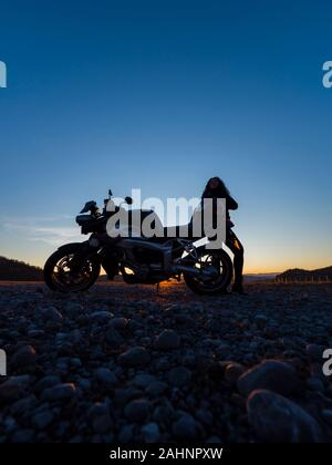 Sunset scenery scenic female motorcycle driver stretching her legs standing besides next to behind vehicle - Stock Photo