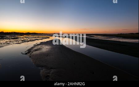 Aberlady Nature Reserve, East Lothian, Scotland, United Kingdom, 31st December 2019. UK Weather: The year draws to an end with a beautiful sunny but very cold day on the coastline of the Firth of Forth on New Year's Eve with an orange sunset over the mudflats at low tide - Stock Photo