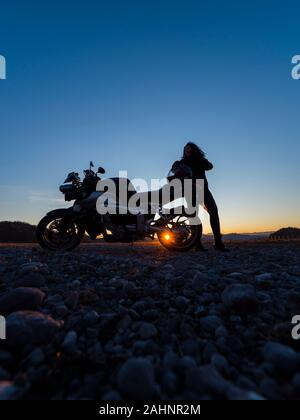 Sunset scenery scenic female motorcycle driver stretching her legs standing besides next to behind vehicle setting sun peek - Stock Photo