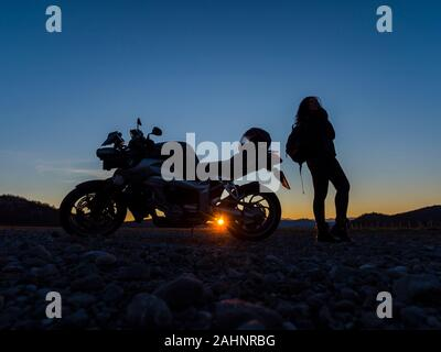 Sunset scenery scenic female motorcycle driver stretching her legs standing besides next to vehicle holding hold traveling rucksack setting sun peek - Stock Photo