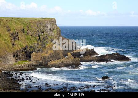 Dramatic basalt coastline with waves breaking on the rocks and a blue sky with puffy white clouds, Antrim Coast, County Antrim, Northern Ireland, UK.