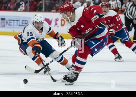 Washington, United States. 31st Dec, 2019. New York Islanders defenseman Devon Toews (25) challenges Washington Capitals defenseman Nick Jensen (3) for the puck during the first period at Capital One Arena in Washington, DC on Tuesday, December 31, 2019. The Washington Capitals finish the decade as the winningest team in the NHL with 465 wins since 2010. Photo by Alex Edelman/UPI Credit: UPI/Alamy Live News - Stock Photo
