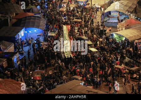 Baghdad, Iraq. 31st Dec, 2019. People hold a large Iraqi flag as they gather at Tahrir Square to celebrate the 2020 New Year's Eve. Credit: Ameer Al Mohmmedaw/dpa/Alamy Live News - Stock Photo