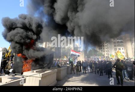Baghdad, Iraq. 31st Dec, 2019. Protesters burn property in front of the U.S. embassy compound, in Baghdad, Iraq, Tuesday, December. 31, 2019. Dozens of angry Iraqi Shiite militia supporters broke into the U.S. Embassy compound in Baghdad on Tuesday after smashing a main door and setting fire to a reception area, prompting tear gas and sounds of gunfire. Witnesses said. Photo by Humam Mohamed /UPI Credit: UPI/Alamy Live News - Stock Photo