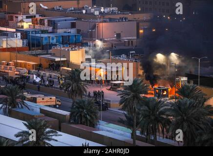 Baghdad, Iraq. 31st Dec, 2019. Protestors set fire to an entry control point at the U.S. Embassy in Baghdad, Iraq, on December 31, 2019. Photo by Staff Sgt. Desmond Cassell/U.S. Army/UPI Credit: UPI/Alamy Live News - Stock Photo