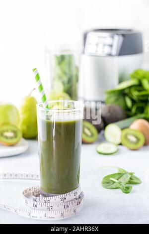 A close up view of a tall glass of green smoothie with a measuring tape around it and the fruits and vegetables and blender in behind. Weight loss and - Stock Photo