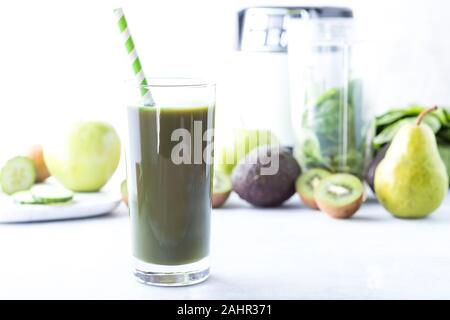 a tall glass of fresh green smoothie with green fruits and vegetables and the blender in behind. Weight loss concept. - Stock Photo