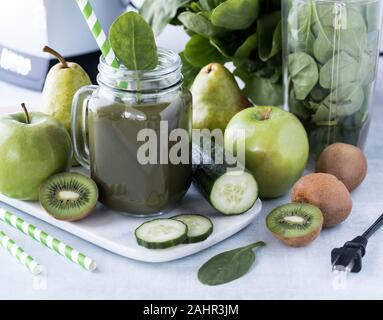 A close up of a glass jar mug filled with green smoothie surrounded by green fruits and vegetables as well as the blender. - Stock Photo