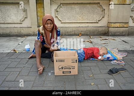 jakarta, indonesia – 2019.12.20: a young woman beggar with wounded leg and her baby on the pavement of jalan kebon kacang raya in the city centre Stock Photo