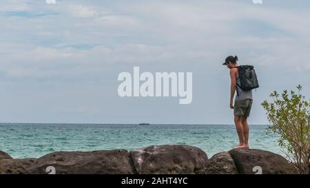 A backpacker is hiking along the coast, cloudy weather, ocean and rocks - Stock Photo