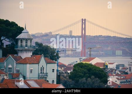 Lisbon panoramic view. Colorful walls of the buildings of Lisbon, with orange roofs and the 25th of April bridge in the background, at sunset. Travel - Stock Photo