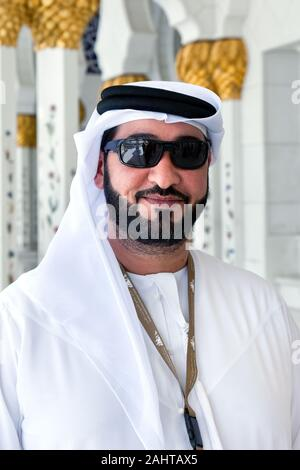 Arabic businessman with sunglasses wearing kandora. Portrait of traditional emirati man at the Grand Mosque of Abu Dabi - Stock Photo