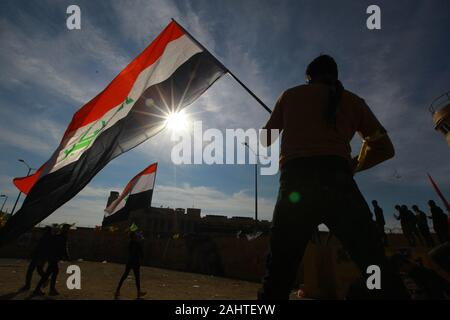 Baghdad, Iraq. 01st Jan, 2020. A protester holds an Iraqi flag during the sit-in in front of the US embassy against deadly US airstrikes on sites of a Shiite militia. Iraqi mourners on Tuesday stormed the building of the US embassy in Baghdad's heavily fortified Green Zone. Credit: Ameer Al Mohmmedaw/dpa/Alamy Live News - Stock Photo