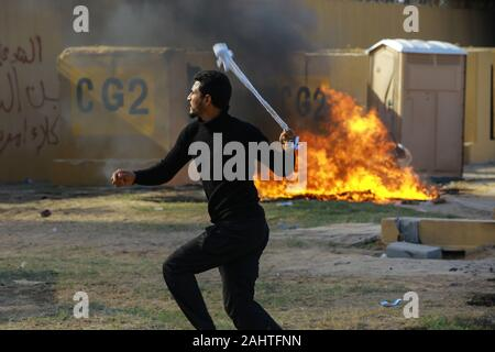 Baghdad, Iraq. 01st Jan, 2020. A protester throws a stone during the sit-in in front of the US embassy against deadly US airstrikes on sites of a Shiite militia. Iraqi mourners on Tuesday stormed the building of the US embassy in Baghdad's heavily fortified Green Zone. Credit: Ameer Al Mohmmedaw/dpa/Alamy Live News - Stock Photo