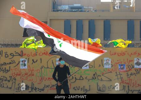 Baghdad, Iraq. 01st Jan, 2020. A protester holds an Iraqi flag during the sit-in against deadly US airstrikes on sites of a Shiite militia in front of the US embassy. Iraqi mourners on Tuesday stormed the building of the US embassy in Baghdad's heavily fortified Green Zone. Credit: Ameer Al Mohmmedaw/dpa/Alamy Live News - Stock Photo