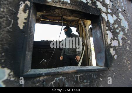 Baghdad, Iraq. 01st Jan, 2020. A protester stands inside a burned checkpoint during the sit-in against deadly US airstrikes on sites of a Shiite militia in front of the US embassy. Iraqi mourners on Tuesday stormed the building of the US embassy in Baghdad's heavily fortified Green Zone. Credit: Ameer Al Mohmmedaw/dpa/Alamy Live News - Stock Photo