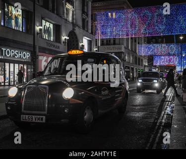 New Year on Oxford Street  with the iconic London black cab. - Stock Photo