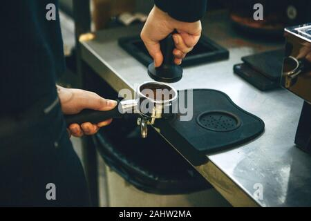 Barista presses ground coffee using tamper. Close-up view on hands with portafilter - Stock Photo