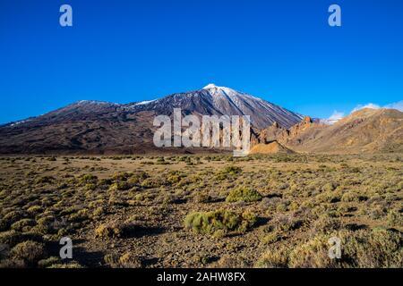 Spain, Tenerife, Volcanic lava nature landscape and some green plants in rocky caldera desert surrounding snow covered peak of mount teide volcano - Stock Photo
