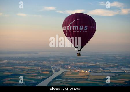 The Ghent-Terneuzen canal passes Sluiskil, going to the locks. A hot air balloon with publicity of telecommunications group Proximus flies high. - Stock Photo