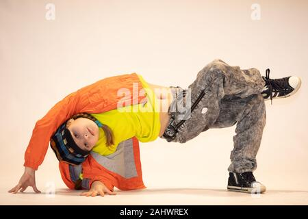 girl in a unique dance position, breakdance kid, a little girl performs breakdance, a child in a unique acrobatic dance pose - Stock Photo